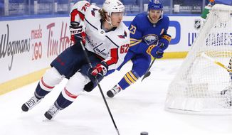 Washington Capitals forward Carl Hagelin (62) carries the puck past Buffalo Sabres forward Sam Reinhart (23) during the first period of an NHL hockey game, Friday, Jan. 15, 2021, in Buffalo, N.Y. (AP Photo/Jeffrey T. Barnes)