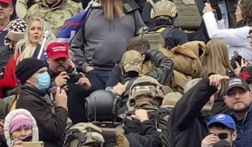 """In this Jan. 6, 2021 image from video provided by Robyn Stevens Brody, a line of men wearing helmets and olive drab body armor walk up the marble stairs outside the U.S. Capitol in Washington in an orderly single-file line, each man holding the jacket collar of the man ahead. The formation, known as """"Ranger File,"""" is standard operating procedure for a combat team """"stacking up"""" to breach a building. (Robyn Stevens Brody via AP)"""