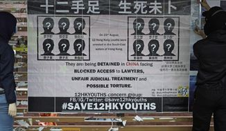 "FILE - In this Sept. 29, 2020, file photo, university students put up posters to demand of releasing the 12 Hong Kong activists detained at sea by Chinese authorities, at ""Lennon Wall"" in the University of Hong Kong. Lu Siwei, who represented one of 12 Hong Kong activists who tried to flee to Taiwan, had his license revoked by the Sichuan Provincial Justice Department in a formal notice given Friday, Jan. 15, 2021. (AP Photo/Kin Cheung, File)"