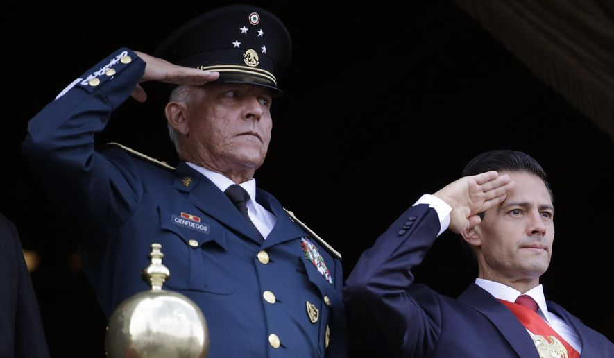 FILE - In this Sept. 16, 2016 file photo, Defense Secretary Gen. Salvador Cienfuegos, left, and Mexico's President Enrique Pena Nieto, salute during the annual Independence Day military parade in Mexico City's main square. The U.S. Justice Department is dropping its drug trafficking and money laundering against former Mexican defense secretary Gen. Salvador Cienfuegos, Attorney General William Barr said Tuesday, Nov. 17, 2020. (AP Photo/Rebecca Blackwell, File)