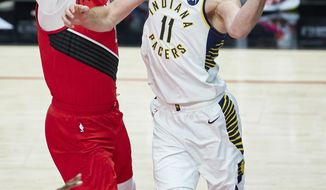 Indiana Pacers forward Domantas Sabonis, right, passes the ball away from Portland Trail Blazers center Jusuf Nurkic during the first half of an NBA basketball game in Portland, Ore., Thursday, Jan. 14, 2021. (AP Photo/Craig Mitchelldyer)