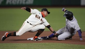 Colorado Rockies' Garrett Hampson, right, is tagged out by San Francisco Giants second baseman Donovan Solano trying to stretch his single during the seventh inning of a baseball game in San Francisco, Tuesday, Sept. 22, 2020. (AP Photo/Jeff Chiu)