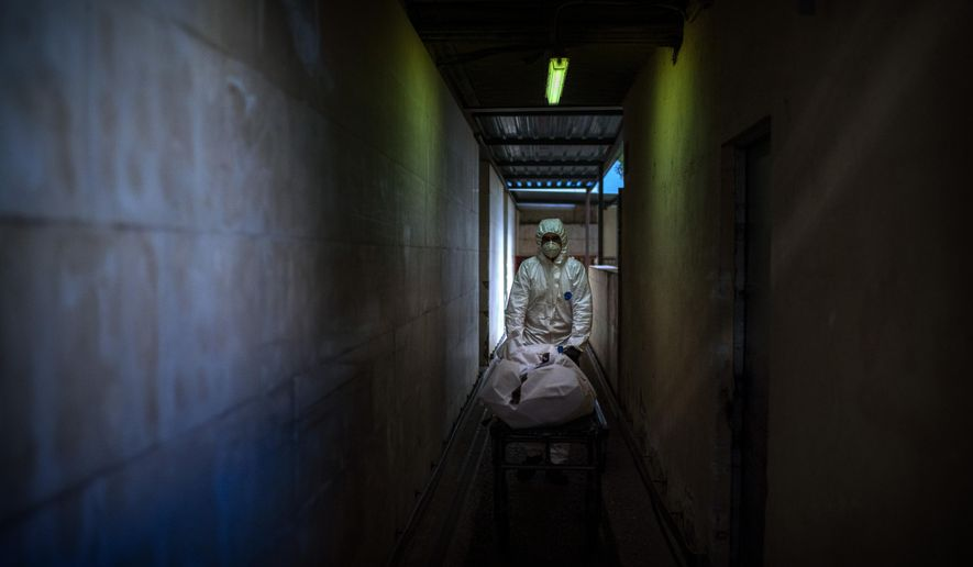 FILE - In this Nov. 5, 2020, file photo, mortuary worker transports the body of a COVID-19 victim on a stretcher at the morgue of a hospital in Barcelona, Spain. (AP Photo/Emilio Morenatti, File)