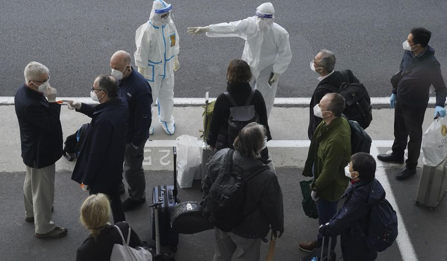 In this Jan. 14, 2021, file photo, a worker in protective coverings directs members of the World Health Organization (WHO) team on their arrival at the airport in Wuhan in central China's Hubei province. A global team of researchers arrived Thursday in the Chinese city where the coronavirus pandemic was first detected to conduct a politically sensitive investigation into its origins amid uncertainty about whether Beijing might try to prevent embarrassing discoveries. (AP Photo/Ng Han Guan, File)