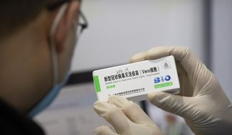 A medical worker shows the box for a coronavirus vaccine to a patient at a vaccination facility in Beijing, Friday, Jan. 15, 2021. A city in northern China is building a 3,000-unit quarantine facility to deal with an anticipated overflow of patients as COVID-19 cases rise ahead of the Lunar New Year travel rush. (AP Photo/Mark Schiefelbein)