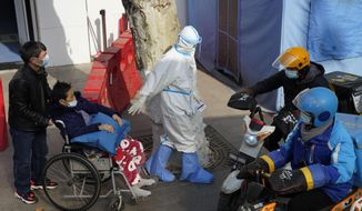 A medical worker in protector overall escorts a patient in wheelchair from the fever screening department of the Tongji Hospital which was at the frontline of the China's fight against the coronavirus in Wuhan in central China's Hubei province on Friday, Jan. 15, 2021. The WHO team of international researchers that arrived in the central Chinese city of Wuhan on Thursday hopes to find clues to the origin of the COVID-19 pandemic. (AP Photo/Ng Han Guan)