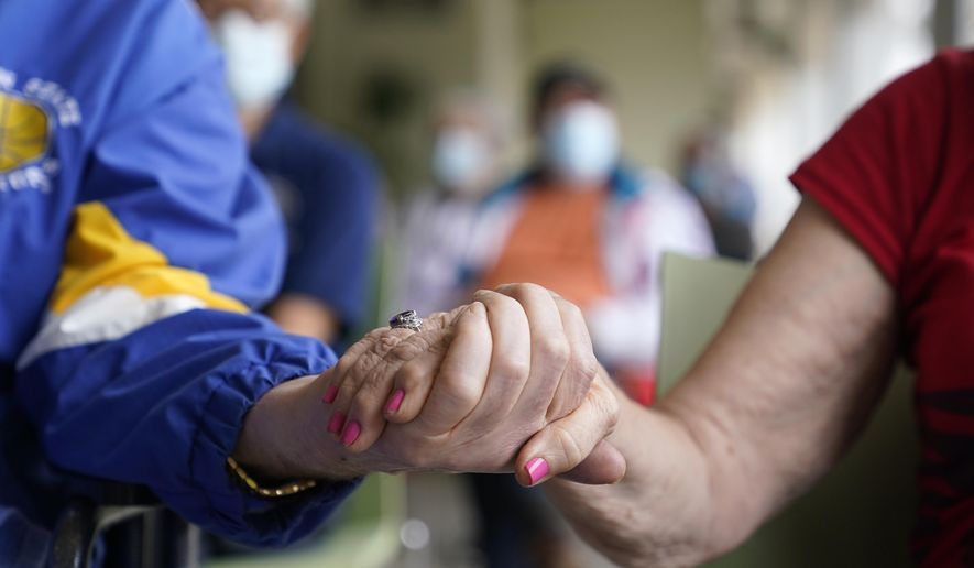 FILE - In this Jan. 12, 2021, file photo residents Ken Fishman, 81, left, and Esther Wallach, 82, right, hold hands as they wait in line for the Pfizer-BioNTech COVID-19 vaccine at the The Palace assisted living facility in Coral Gables, Fla. An ongoing study suggests that older American adults are showing resilience and perseverance despite struggles with loneliness and isolation during the pandemic. (AP Photo/Lynne Sladky, File)