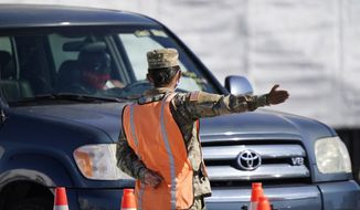 A Florida National Guardsman directs traffic at a COVID-19 testing site, Wednesday, Jan. 6, 2021, outside Hard Rock Stadium in Miami Gardens, Fla. First responders and people over 65 years-old began receiving the COVID-19 vaccine Wednesday during a trial run of the site which will open to seniors at a later date. (AP Photo/Wilfredo Lee)