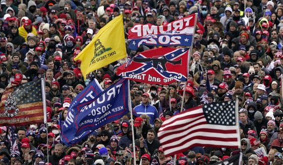 Photos and video of the Capitol assault showed rioters with clothing, emblems and flags identifying themselves as members of the conspiracy group QAnon, the loosely allied alt-right America First group, and militias such as Three Percenters, the Proud Boys and the Oath Keepers. (Associated Press/File)