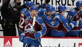 Colorado Avalanche left wing Gabriel Landeskog, front, smiles after he was congratulated as he passed the team box after scoring his second goal in the second period of an NHL hockey game against the St. Louis Blues, Friday, Jan. 15, 2021, in Denver. (AP Photo/David Zalubowski)