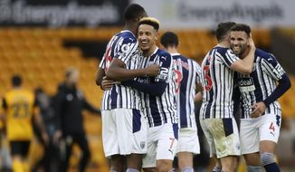 West Bromwich Albion's Callum Robinson, 2nd left, celebrates with teammates after the English Premier League soccer match between Wolverhampton Wanderers and West Bromwich Albion at the Molineux Stadium in Wolverhampton, England, Saturday, Jan. 16, 2021. (Carl Recine/Pool via AP)