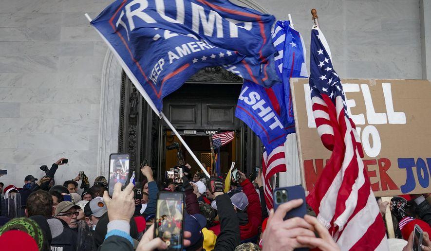 In this Jan. 6, 2021, file photo rioters break into the Capitol in Washington. (AP Photo/John Minchillo, File)
