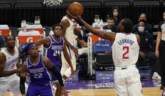 Los Angeles Clippers forward Kawhi Leonard, right, goes for a layup as Sacramento Kings' Richaun Holmes, second from left, and Buddy Hield, third from left, watch during the first quarter of an NBA basketball game in Sacramento, Calif., Friday, Jan. 15, 2021. (AP Photo/Rich Pedroncelli)