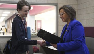 Kankakee High School freshman David Love accepts a letter of recognition from U.S. Rep. Robin Kelly for his project that won the 2019 Congressional App Challenge for Illinois' 2nd Congressional District, Monday, Feb. 24, 2020 in Kankakee, Ill.. More than 2,000 apps created by more than 10,000 students were submitted to the competition nationally. (Tiffany Blanchette/The Daily Journal via AP)