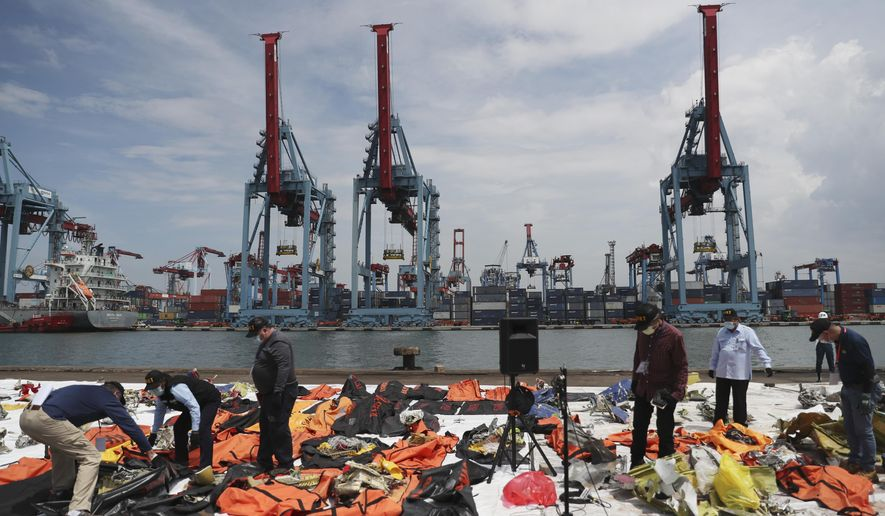 Investigators from Indonesian National Transportation Safety Committee (KNKT) and U.S. National Transportation Safety Board (NTSB) inspect debris found in the waters around the location where a Sriwijaya Air passenger jet crashed, at the search and rescue command center at Tanjung Priok Port in Jakarta, Indonesia Saturday, Jan. 16, 2021. (AP Photo/Achmad Ibrahim)