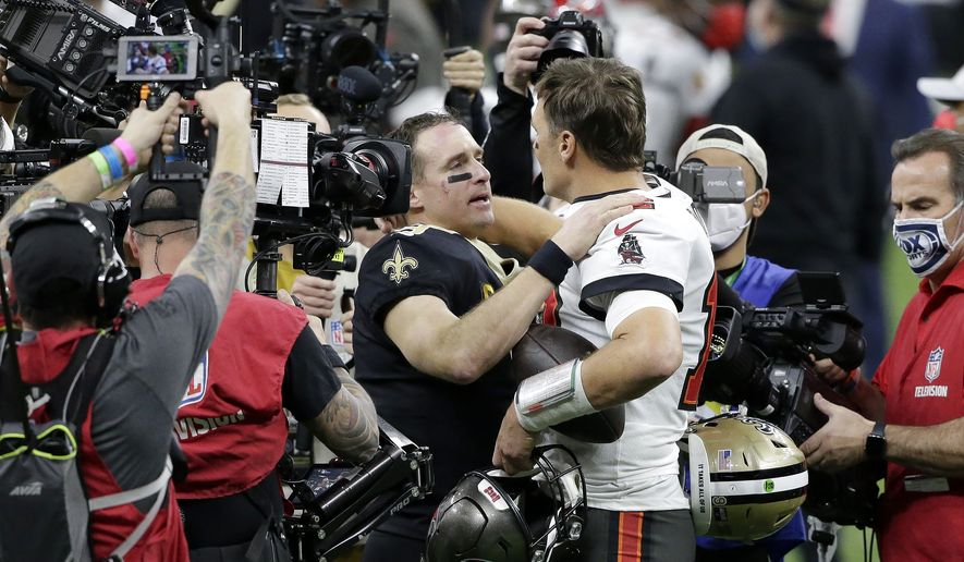New Orleans Saints quarterback Drew Brees, center left, speaks with Tampa Bay Buccaneers quarterback Tom Brady after an NFL divisional round playoff football game, Sunday, Jan. 17, 2021, in New Orleans. The Buccaneers won 30-20. (AP Photo/Butch Dill)