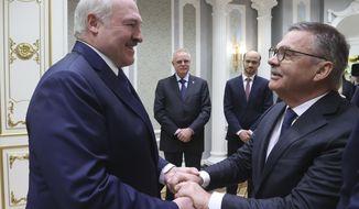 Belarusian President Alexander Lukashenko, left, greets International Ice Hockey Federation President Rene Fasel during their meeting in Minsk, Belarus, Monday, Jan. 11, 2021. (Nikolai Petrov/BelTA Pool Photo via AP)