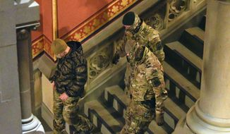 New York state Police wearing tactical gear patrol the hallways of the state Capitol prior to a planned President Trump protest rally ahead of the inauguration of President-elect Joe Biden and Vice President-elect Kamala Harris Sunday, Jan. 17, 2021, in Albany, N.Y. (AP Photo/Hans Pennink)