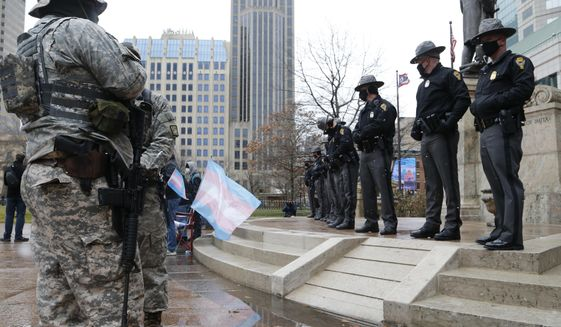 Ohio state troopers provide security at the Ohio Statehouse as armed protestors look on Sunday, Jan. 17, 2021, in Columbus, Ohio. Security was stepped up at statehouses across the U.S. after FBI warnings of potential armed protests at all 50 state capitols and in Washington, D.C. (AP Photo/Jay LaPrete)