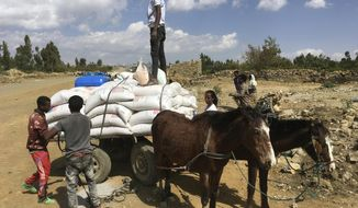 """In this Tuesday Jan. 12, 2021 photo provided by the Catholic Relief Services, people affected by the conflict in Tigray load food aid provided by USAID and Catholic Relief Services onto a donkey cart to be tansported to their home, outside Mekele, Ethiopia. From """"emaciated"""" refugees to crops burned on the brink of harvest, starvation threatens the survivors of more than two months of fighting in Ethiopia's Tigray region. Authorities say more than 4.5 million people, or nearly the entire population, need emergency food. The first humanitarian workers to arrive after weeks of pleading with Ethiopia for access describe weakened children dying from diarrhea after drinking from rivers, and shops that were looted or depleted weeks ago. (Catholic Relief Services via AP)"""