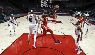 Atlanta Hawks center Clint Capela, center, shoots between Portland Trail Blazers forward Carmelo Anthony, left, and guard CJ McCollum, right, during the first half of an NBA basketball game in Portland, Ore., Saturday, Jan. 16, 2021. (AP Photo/Craig Mitchelldyer)