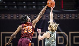 Virginia Tech forward Justyn Mutts (25) blocks a shot from Wake Forest guard Carter Whitt (35) during an NCAA college basketball game Sunday, Jan. 17, 2021, in Winston-Salem, N.C. (Andrew Dye/The Winston-Salem Journal via AP)