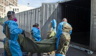 FILE - This Jan. 12, 2021, file photo provided by the LA County Dept. of Medical Examiner-Coroner shows National Guard members assisting with processing COVID-19 deaths and placing them into temporary storage at LA County Medical Examiner-Coroner Office in Los Angeles in Los Angeles. More than 500 people are dying each day in California because of the coronavirus. The death toll has prompted state officials to send more refrigerated trailers to local governments to act as makeshift morgues. State officials said Friday they have helped distribute 98 refrigerated trailers to help county coroners store dead bodies. California reported 669 COVID-19 deaths, the second-highest daily death count, on Saturday, Jan. 16, and the nation's most populous county announced it had detected its first case of a more transmissible strain of the coronavirus. Public health authorities in Los Angeles County confirmed its first case of the variant of COVID-19 first detected in the United Kingdom. It was identified in a man who recently spent time in the county. (LA County Dept. of Medical Examiner-Coroner via AP, File)