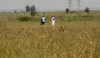 Worshipers pray in open fields, by the side of the road in Katlehong, east of Johannesburg, South Africa, Sunday, Jan. 17, 2021, as faith-based gatherings, are prohibited during the level 3 COVID-19 lockdown. (AP Photo/Themba Hadebe)