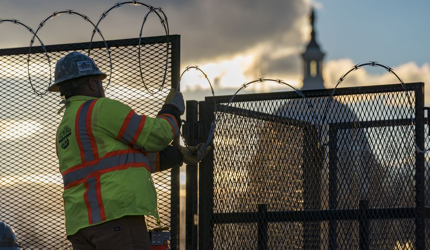 Workers install razor wire atop fencing around the U.S. Capitol perimeter at sunset, in Washington, Monday, Jan. 18, 2021. President-elect Joe Biden will be sworn in as the 46th president of the United States on Wednesday, Jan.  20, extraordinary security following the attack on the Capitol, Jan. 6, by a mob of supporters loyal to President Donald Trump. (AP Photo/J. Scott Applewhite)