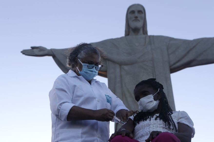 Terezinha da Conceicao, 80, is the first women to receive the COVID-19 vaccine produced by China's Sinovac Biotech Ltd, during the start of the vaccination program in front of the statue of Cristo Redentor, in the city of Rio de Janeiro, Brazil, Monday, Jan. 18, 2021. (AP Photo/Bruna Prado)