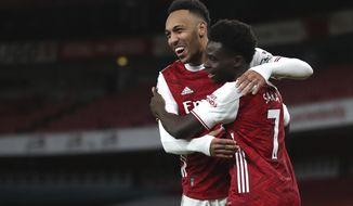 Arsenal's Bukayo Saka, right, celebrates with Pierre-Emerick Aubameyang after scoring his side's second goal during the English Premier League soccer match between Arsenal and Newcastle United at Emirates Stadium in London, England, Monday, Jan.18, 2021. (Catherine Ivill/Pool via AP)