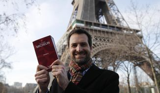 Gwendal Poullennec, head of Le Guide Michelin, poses outside the Eiffel Tower with the 2021 edition Monday, Jan. 18, 2021 in Paris. Michelin will later announce the 2021 winners in a broadcast from the Eiffel Tower. (AP Photo/Francois Mori)