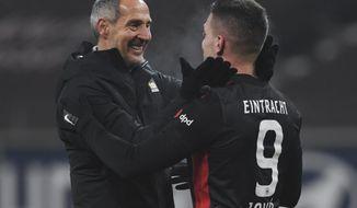 Frankfurt's Luka Jovic, right, and Frankfurt's head coach Adi Huetter, left, celebrate after the German Bundesliga soccer match between Eintracht Frankfurt and FC Schalke 04 in Frankfurt, Germany, Sunday, Jan. 17, 2021. (Arne Dedert/dpa via AP)