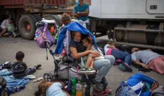 Honduran migrants gather in front of a police roadblock at a highway in Vado Hondo, Guatemala, Guatemala, Sunday, Jan. 17, 2021. Guatemalan police and soldiers launched tear gas and wielded batons and shields against a group of Honduran migrants that tried to push through their roadblock early Sunday. (AP Photo/Sandra Sebastian)