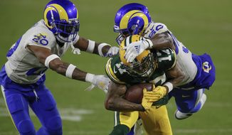 Los Angeles Rams' Samson Ebukam (50) and Rams' Jalen Ramsey stop Green Bay Packers' Davante Adams during an NFL divisional playoff football game Saturday, Jan. 16, 2021, in Green Bay, Wis. The Packers defeated the Rams 32-18 to advance to the NFC championship game. (AP Photo/Matt Ludtke)