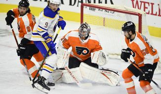 Philadelphia Flyers goaltender Carter Hart, center, looks for the puck as Buffalo Sabres' Jack Eichel (9) is defended by Ivan Provorov (9) and Erik Gustafsson (56) during the first period of an NHL hockey game, Monday, Jan. 18, 2021, in Philadelphia. (AP Photo/Derik Hamilton)
