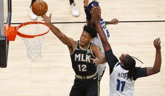 Atlanta Hawks forward De'Andre Hunter (12) goes up for a shot as center Naz Reid (11) and Minnesota Timberwolves forward Jarred Vanderbilt (8) defend in the first half of an NBA basketball game on Monday, Jan. 18, 2021, in Atlanta. (AP Photo/Todd Kirkland)