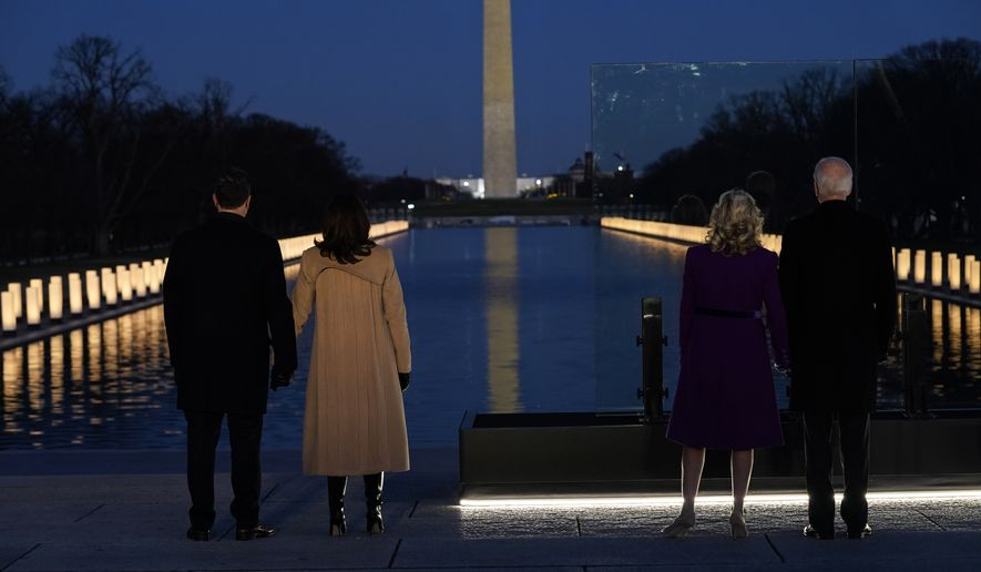 With the Washington Monument in the background, President-elect Joe Biden stands with his wife Jill Biden and Vice President-elect Kamala Harris stands with her husband Doug Emhoff as they look at lights placed around the Lincoln Memorial Reflecting Pool during a COVID-19 memorial Tuesday, Jan. 19, 2021, in Washington. (AP Photo/Evan Vucci)
