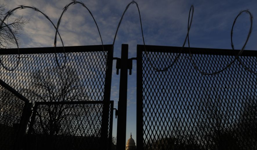 A security fence with barb wire seals a road to the Capitol in preparation for President-elect Joe Biden's inauguration ceremony, Tuesday, Jan. 19, 2021, in Washington. (AP Photo/Rebecca Blackwell)