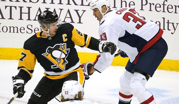 Pittsburgh Penguins' Sidney Crosby (87) is defended by Washington Capitals' Zdeno Chara (33) during the first period of an NHL hockey game in Pittsburgh, Tuesday, Jan. 19, 2021. (AP Photo/Gene J. Puskar)