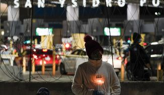 A woman holds a candle during a vigil in support of migrants as she stands at the entrance to the San Ysidro Port of Entry along the border between the United States and Mexico, late Tuesday, Jan. 19, 2021, in Tijuana, Mexico. President-elect Joe Biden plans to unveil a sweeping immigration bill on Day One of his administration. It would provide an eight-year path to citizenship for an estimated 11 million people living in the U.S. without legal status, according to a person granted anonymity to discuss the legislation. (AP Photo/Gregory Bull)