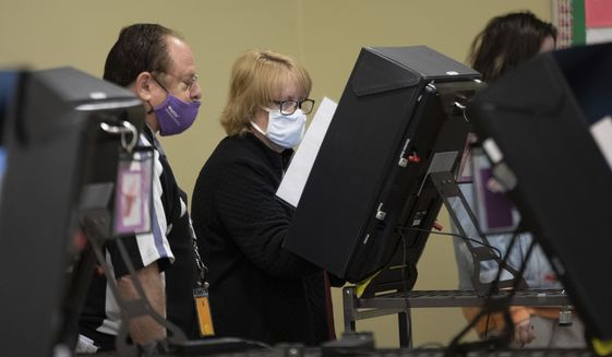 A technician watches as a poll worker tries to use a voting machine after experiencing issues in Georgia's Senate runoff elections at a senior center, Tuesday, Jan. 5, 2021, in Acworth, Ga. (AP Photo/Branden Camp)