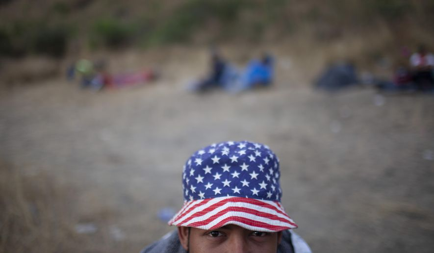 A Honduran migrant wearing a hat with the stars and stripes, poses for a photo at a road block manned by Guatemalan soldiers and police, on the highway in Vado Hondo, Guatemala, Monday, Jan. 18, 2021. Some migrants threw rocks while authorities launched tear gas and pushed the migrants with their riot shields back down the highway. (AP Photo/Sandra Sebastian)