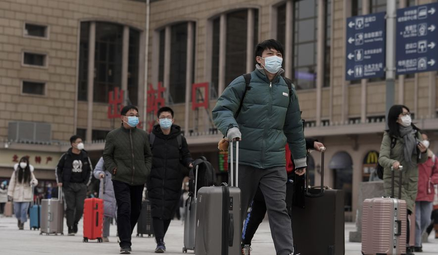 Passenger wearing face masks to help curb the spread of the coronavirus walk out from the Beijing railway station as they arrive in Beijing, Tuesday, Jan. 19, 2021. China is now dealing with coronavirus outbreaks across its frigid northeast, prompting additional lockdowns and travel bans. (AP Photo/Andy Wong)