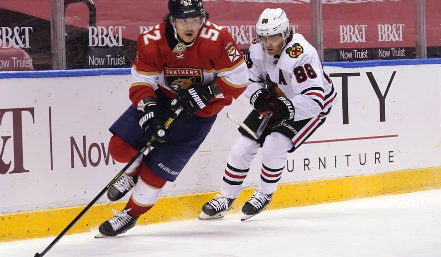 Florida Panthers defenseman MacKenzie Weegar (52) skates ahead of Chicago Blackhawks right wing Patrick Kane (88) during overtime in an NHL hockey game, Tuesday, Jan. 19, 2021, in Sunrise. The Panthers won 5-4. (AP Photo/Marta Lavandier)
