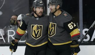 Vegas Golden Knights center Chandler Stephenson, left, embraces left wing Max Pacioretty (67) after Pacioretty scored against the Arizona Coyotes during the second period of an NHL hockey game Monday, Jan. 18, 2021, in Las Vegas. (AP Photo/John Locher)