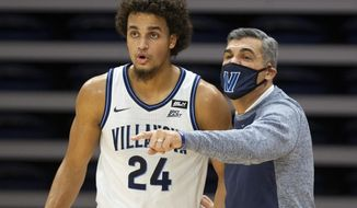 Villanova head coach Jay Wright talks with forward Jeremiah Robinson-Earl (24) during the first half of an NCAA college basketball game against Seton Hall, Tuesday, Jan. 19, 2021, in Villanova, Pa. (AP Photo/Laurence Kesterson)