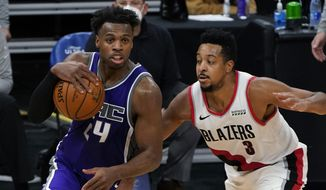 Sacramento Kings guard Buddy Hield, left, drives against Portland Trail Blazers guard CJ McCollum during the second half of an NBA basketball game in Sacramento, Calif., Wednesday, Jan. 13, 2021. The Trail Blazers won 132-126. (AP Photo/Rich Pedroncelli)