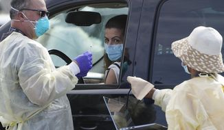 People wait inside their vehicles in line at a mass COVID-19 vaccination site outside The Forum in Inglewood, Calif., Tuesday, Jan. 19, 2021. (AP Photo/Damian Dovarganes)
