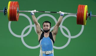 In this Wednesday, Aug. 10, 2016 file photo, Nijat Rahimov, of Kazakhstan, sets a world record with a lift of 214kg during the men's 77kg weightlifting competition at the 2016 Summer Olympics in Rio de Janeiro, Brazil. (AP Photo/Mike Groll, File) **FILE**